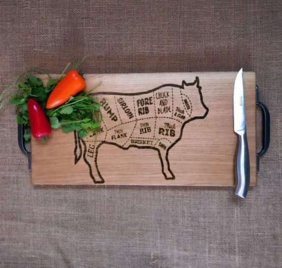 Oak Chopping Board with Cast Iron Handles and Cow Design Engraved onto Surface Pictured with Sweet Peppers