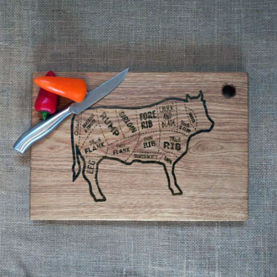 Oak Chopping Board with No Handles and Cow Design Engraved onto Surface Pictured with Sweet Peppers