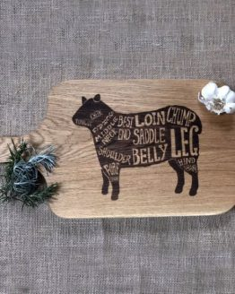 Oak Chopping Board with Wooden Handle with Lamb Sheep Design Engraved onto Surface Pictured with Onion and Rosemary