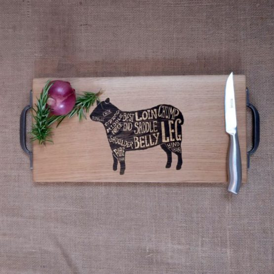 Oak Chopping Board with Cast Iron Handles with Lamb Sheep Design Engraved onto Surface Pictured with Onion and Rosemary