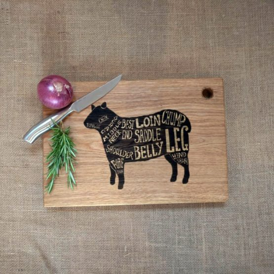 Oak Chopping Board with Lamb Sheep Design Engraved onto Surface Pictured with Onion and Rosemary
