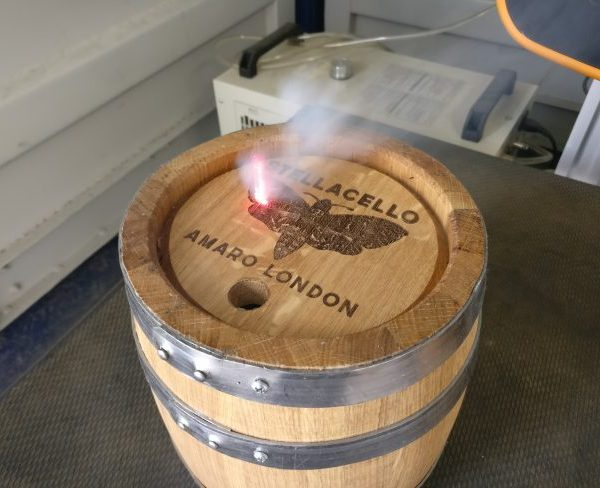 In action, Stella Cello Liqueur company's logo engraved on to an oak barrel keg