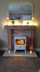 Light Oak Beam Fire Surround above white log burner - Heavily Worked